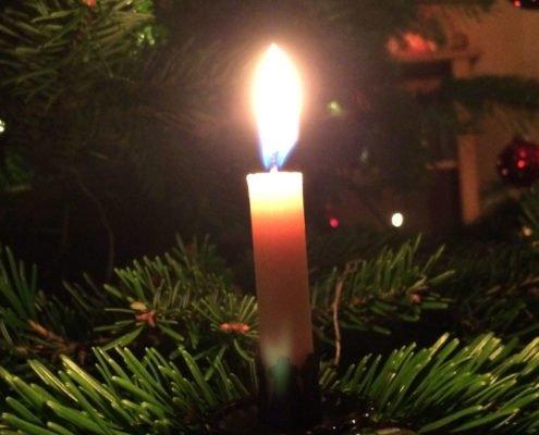 Brennende Kerze an einem Weihnachtsbaum